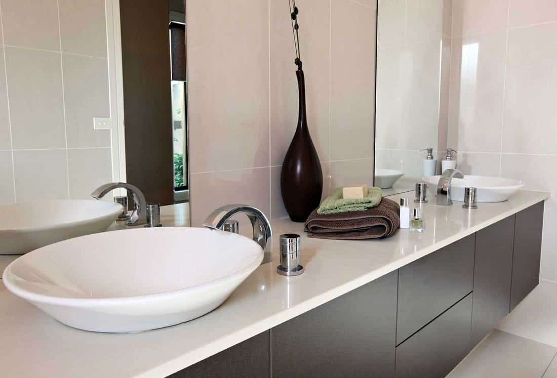 Contemporary bathroom with brown cabinets, white double sink and towels on countertop