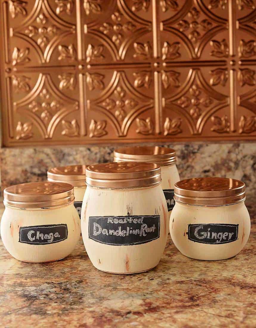 Copper painted jars for tea with a copper tile backsplash