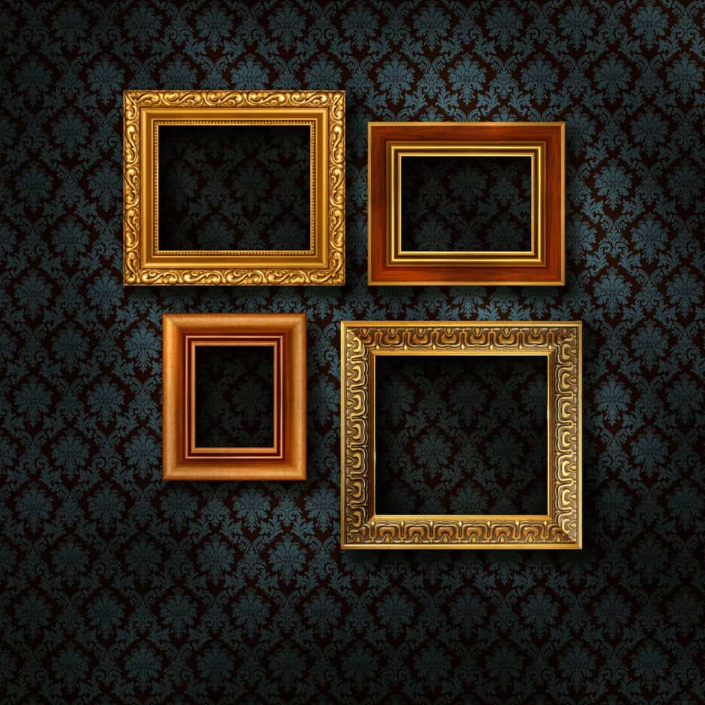 Different sizes of gold plated picture frames mounted on a floral wallpaper