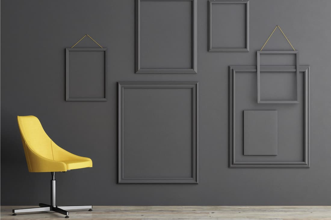 Empty frame composition on grey wall, yellow upholstered chair
