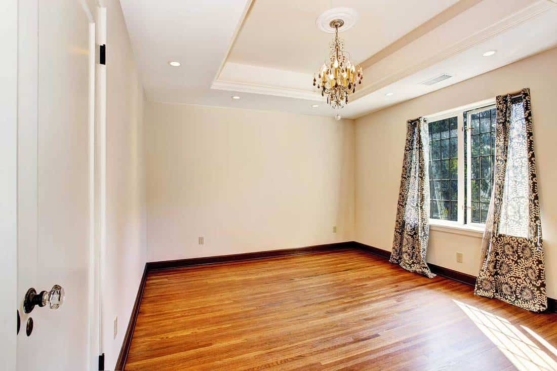 Empty room interior in soft ivory with hardwood floor and coffered ceiling