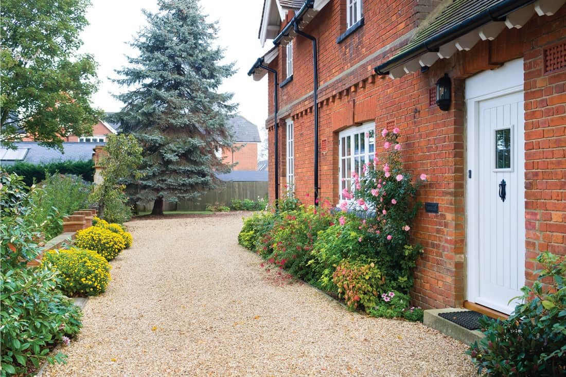 English country house and garden in Autumn with a gravel driveway. The house is Victorian period, with flower borders filled with shrubs and perennials. Edge Your Gravel Driveway With Beautiful Low Flowering Plants