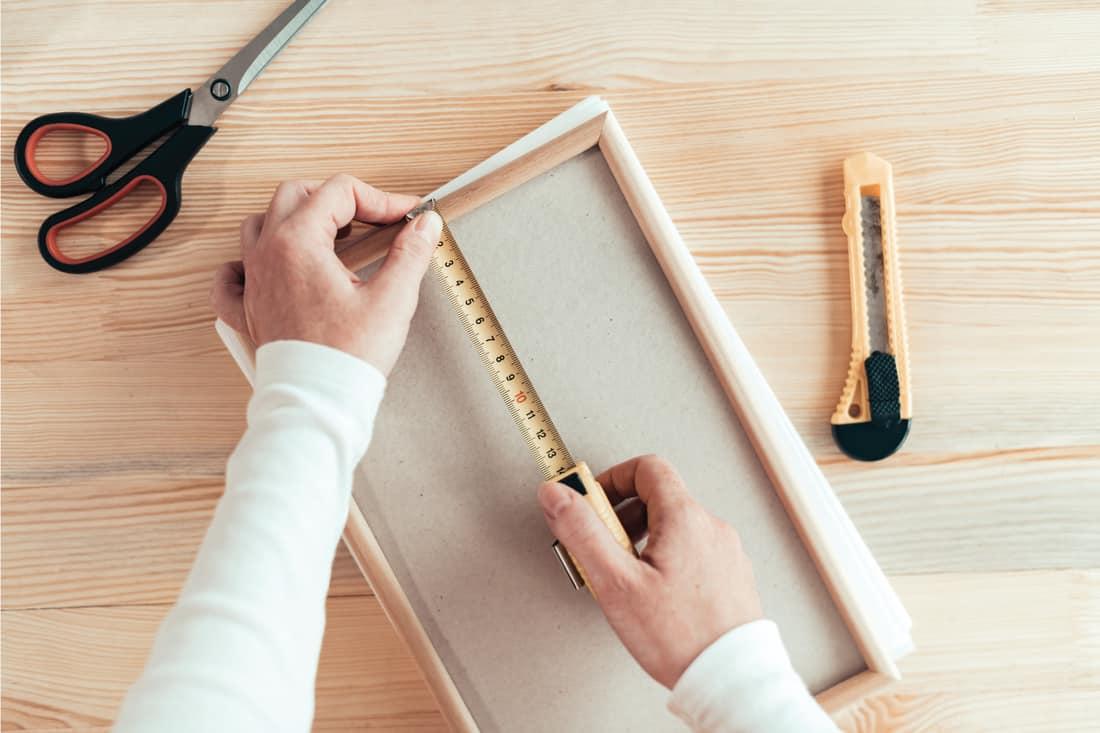 Female carpenter tape measuring picture frame in workshop