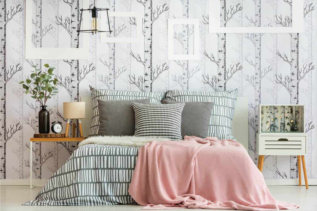 Feminine bedroom interior with forest inspired decorations and geometric bedding