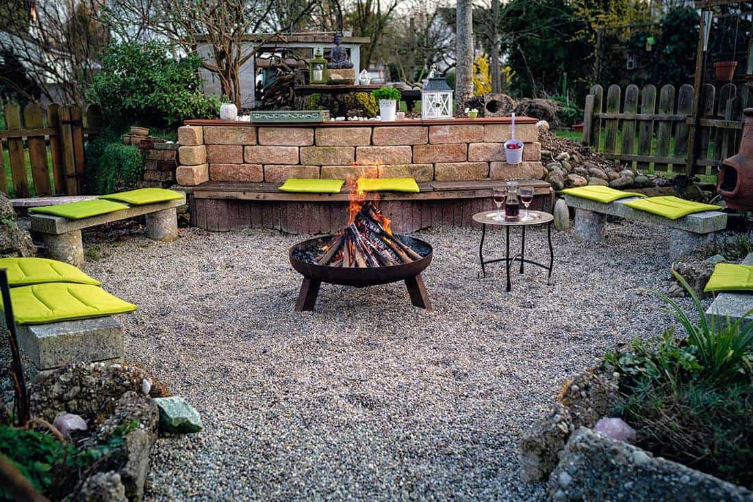 Fire bowl in the garden with stone benches around