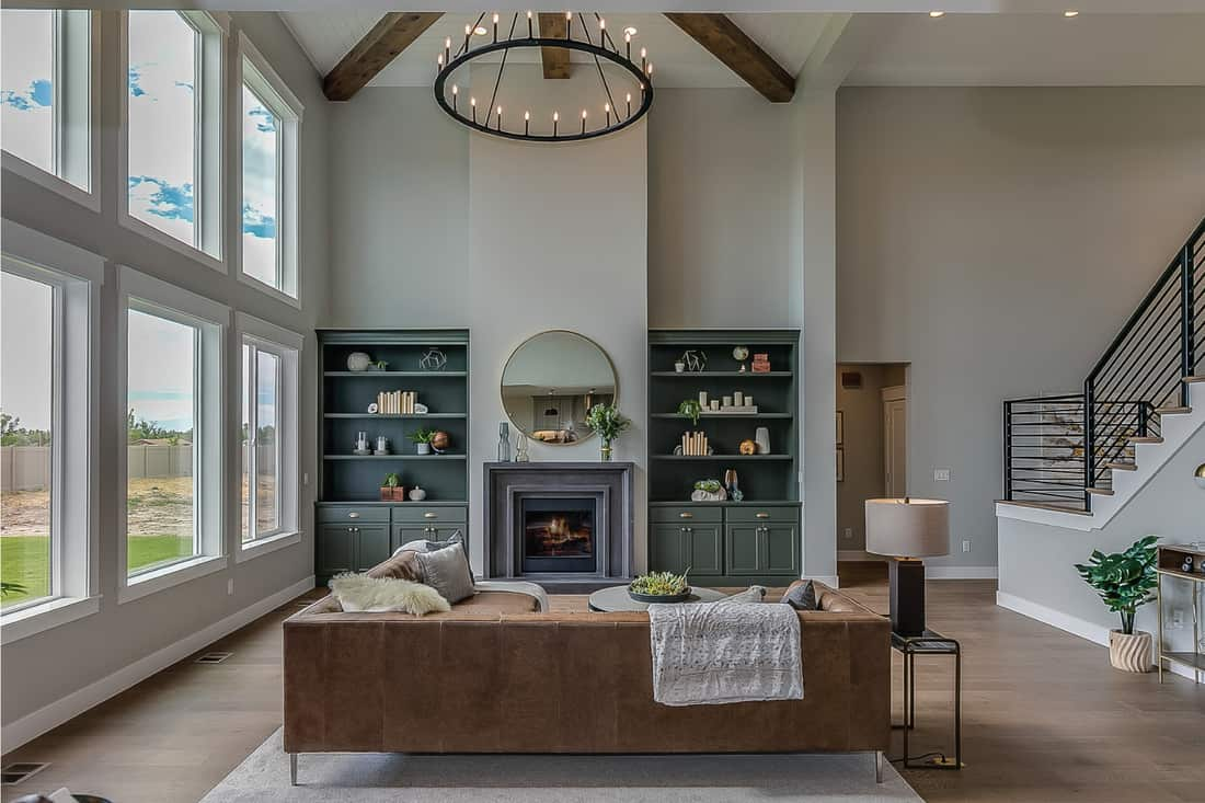 Gorgeous detail in family room with modern furnishings and large chandelier hanging high above the room