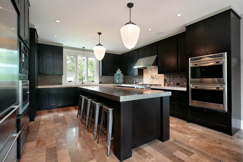 Gorgeous modern contemporary kitchen with laminated flooring, huge dangling lamps, and black painted kitchen cabinetry