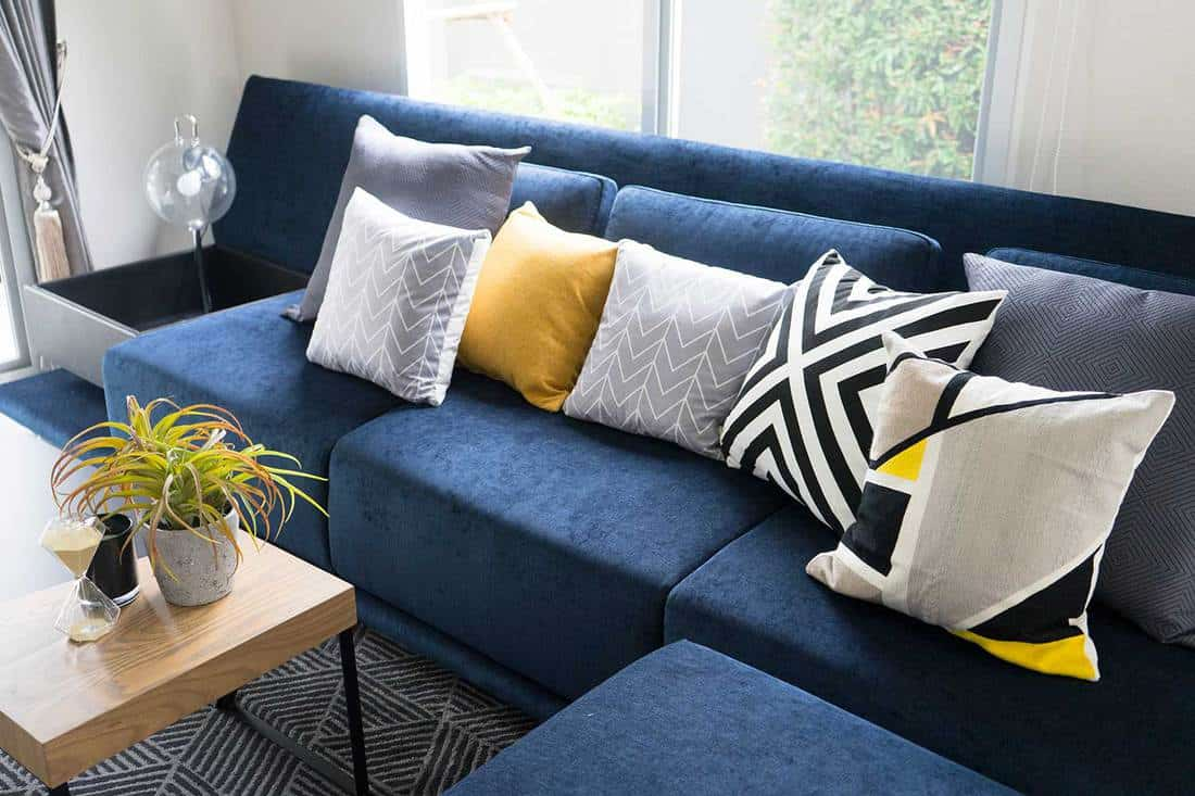 Graphic pattern and yellow pillow setting up on modern blue sofa at home