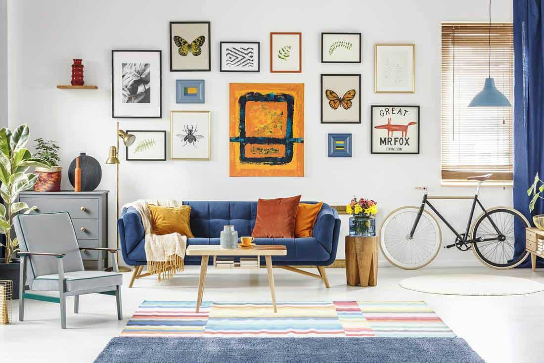 Gray armchair and blue sofa in spacious living room interior with framed artwork on white wall
