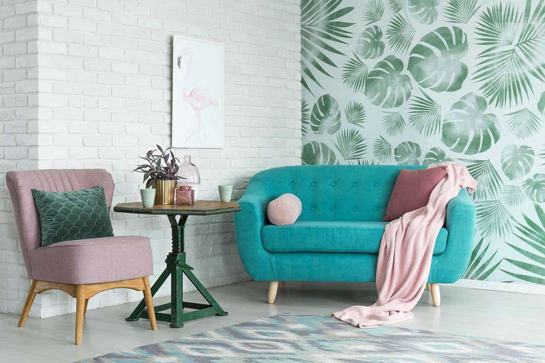Green table with plant between pink chair and blue sofa in floral living room with wallpaper and brick wall