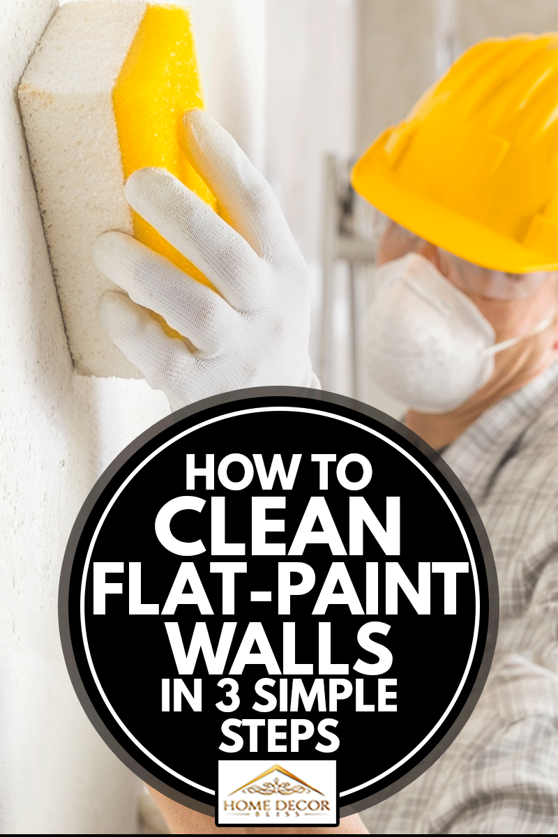 A painter wearing a hardhat and face mask for cleaning and smoothing an interior flat paint wall during construction or renovation work, How To Clean Flat-Paint Walls In 3 Simple Steps