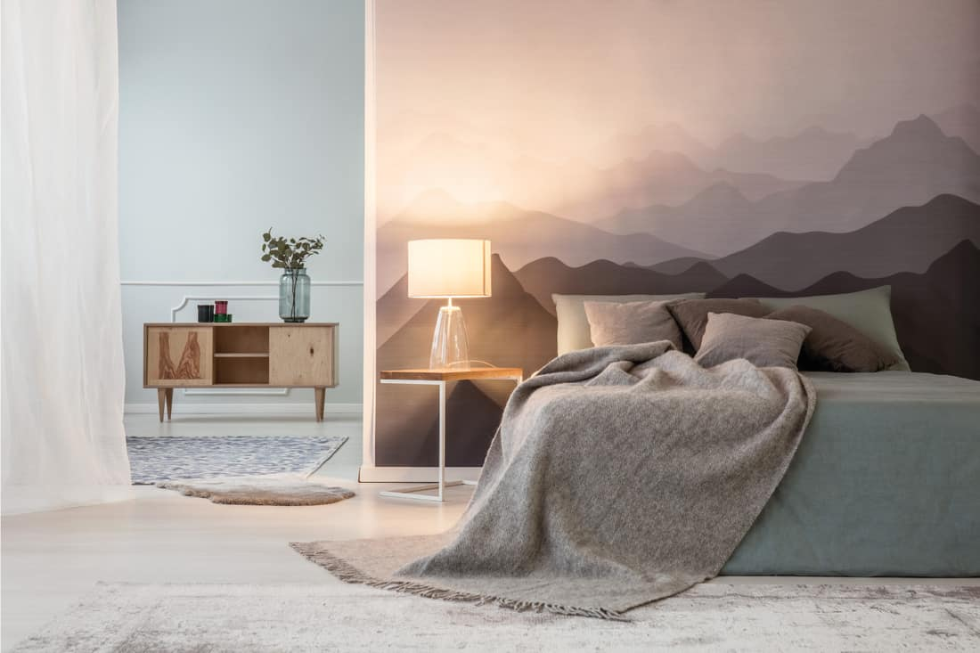 Illuminated mountains lover open space bedroom interior with a wooden cabinet and a gray cozy bed a landscape wallpaper
