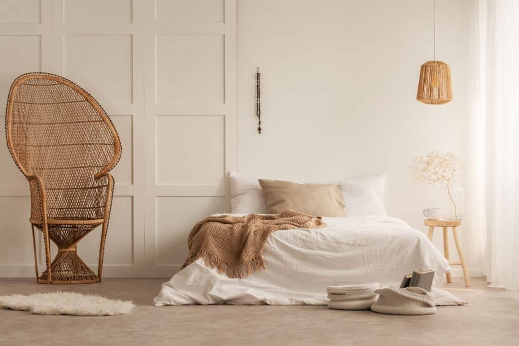 Interior of a cream painted bedroom with white beddings, brown drapes, and a huge rattan accent chair, and