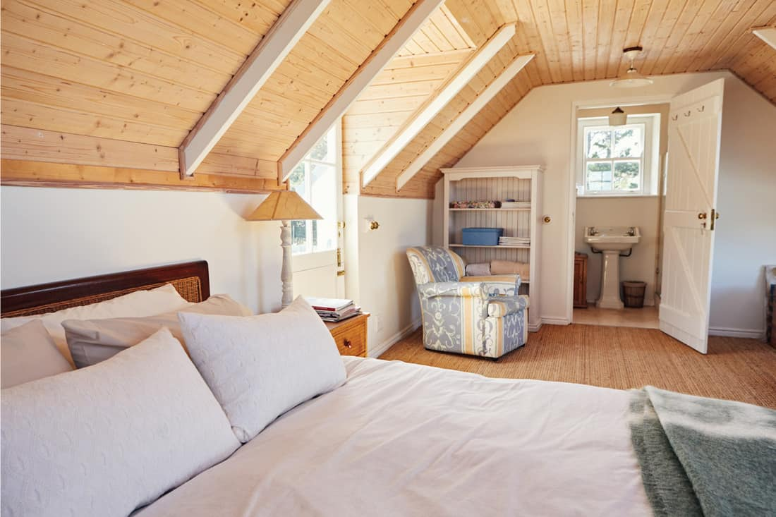 Interior of a comfortable master bedroom with an en suite bathroom in the loft of a contemporary residential home. A Half Bath Is Better Than No Bath