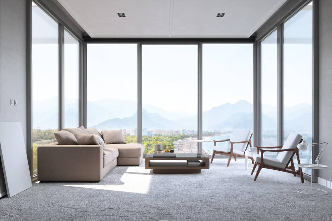 Interior of a contemporary minimalist living room with beautiful mountain, ocean and beach view. windows for walls