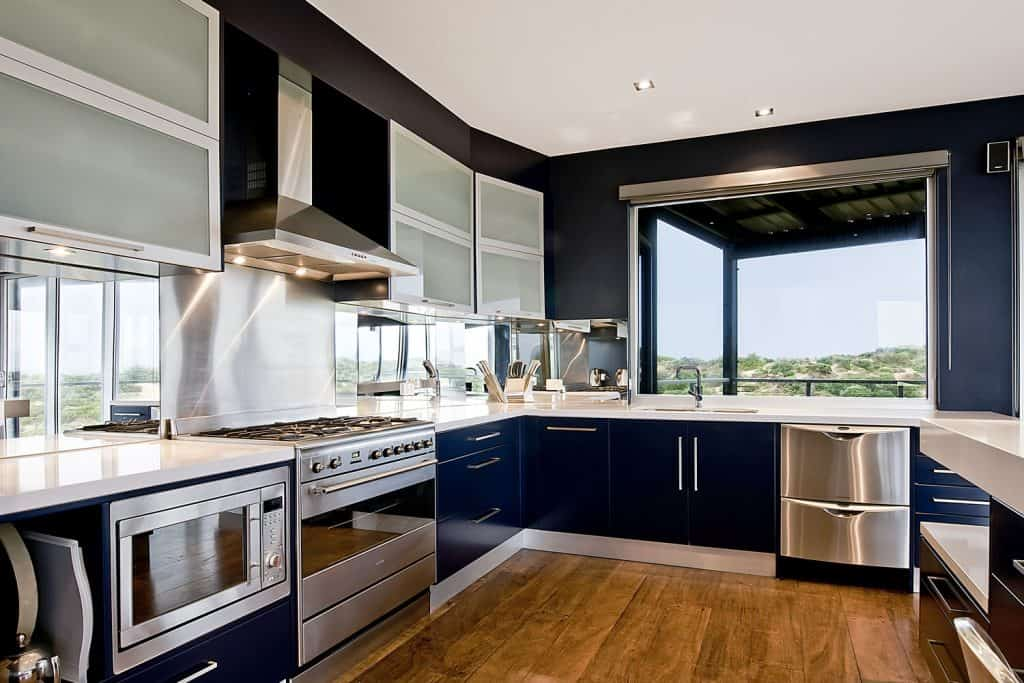 Interior of a dark blue colored kitchen wall and cabinetry with stainless steel kitchen appliances