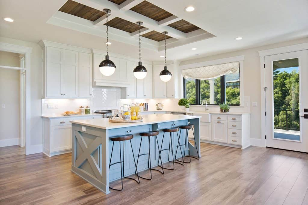 Interior of a gorgeous kitchen area with dangling lamps, wooden laminated flooring, white paneled cabinetry, and white walls