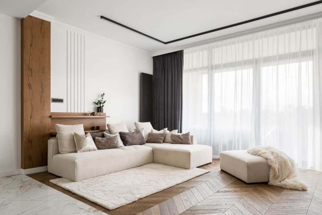 Interior of a gorgeous white themed living room with white curtains, beige colored sectional couch, and wooden laminated flooring
