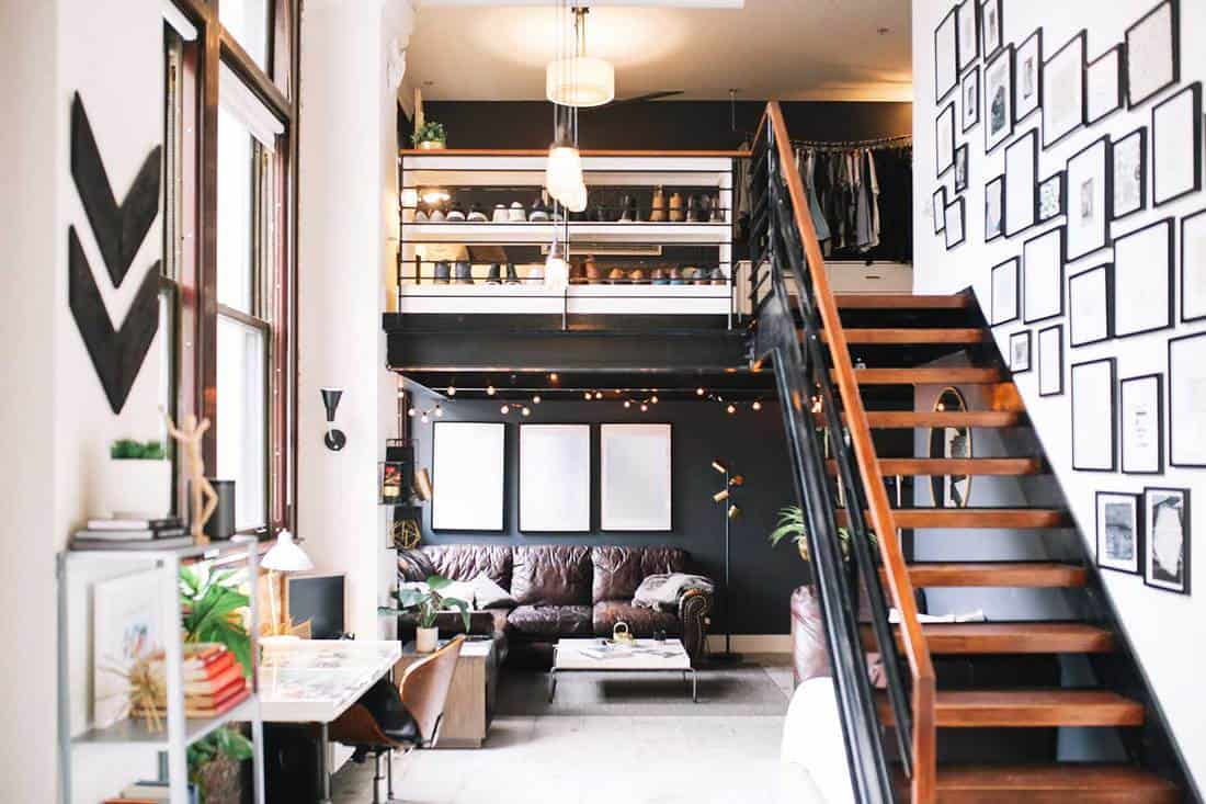 Interior of a large and bright loft apartment with framed photos on the stairs and view of the living room