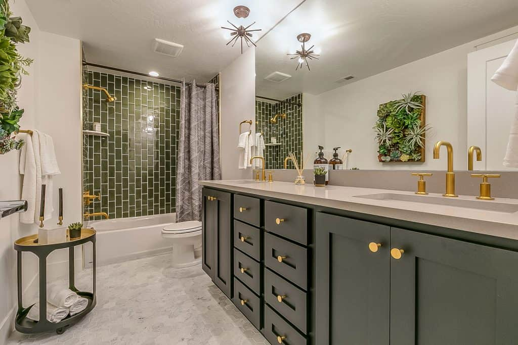 Interior of a luxurious bathroom with a green painted cabinetry, white painted walls, and a window on the background