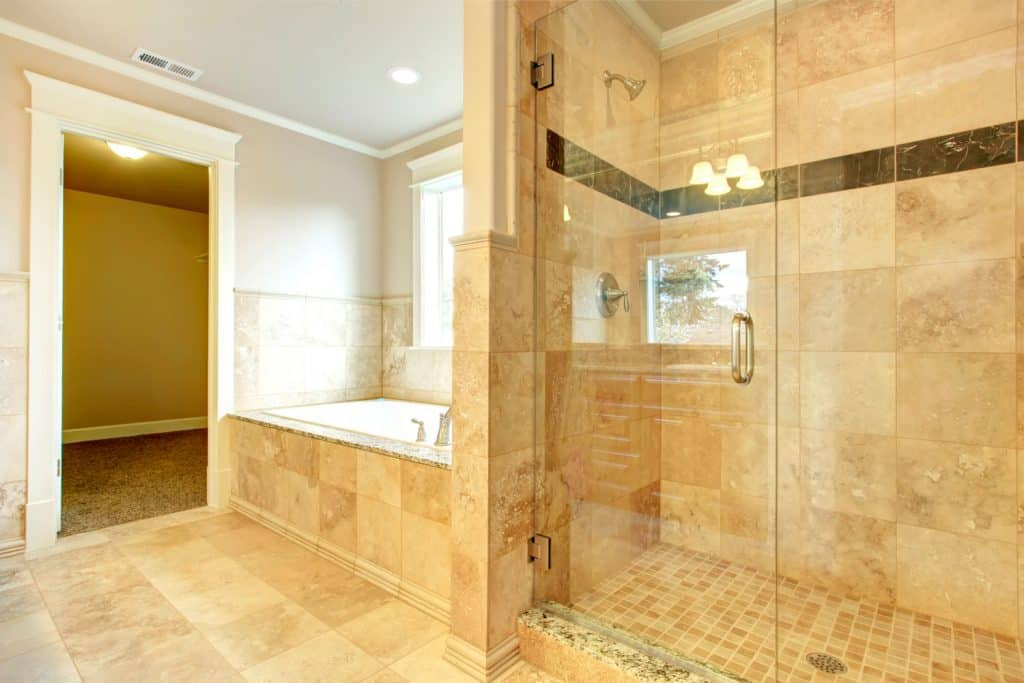 Interior of a luxurious bathroom with white painted walls, glass walled shower area, and beige decorative shower wall, Should Bathtub Tile Go To The Ceiling?