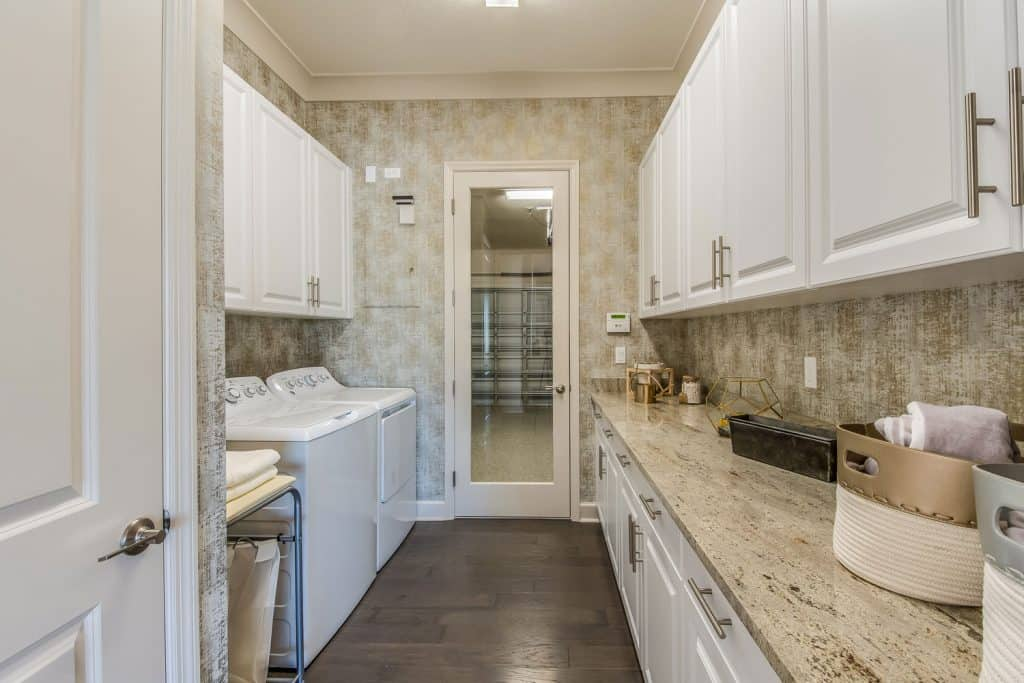 Interior of a luxurious laundry room with wooden laminated flooring, white painted cabinetry, and two washing machines