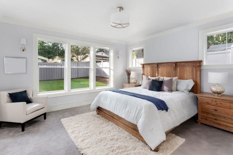 Interior of a modern bedroom with white painted walls, a huge wooden bed with white beddings, and a carpeted flooring with a beige area rug, Can You Put A Rug On Top Of Carpet In The Living Room?