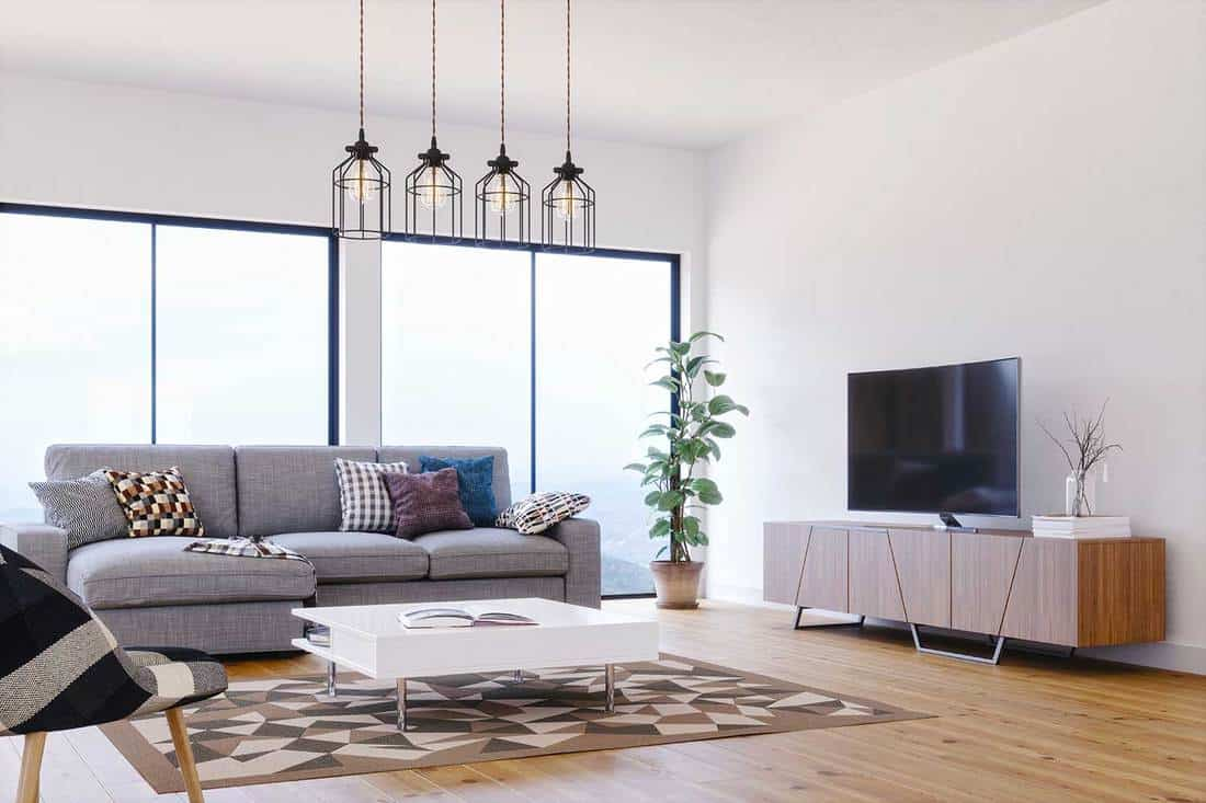 Interior of a modern, bright and airy Scandinavian design living room with wooden floor and gray sofa