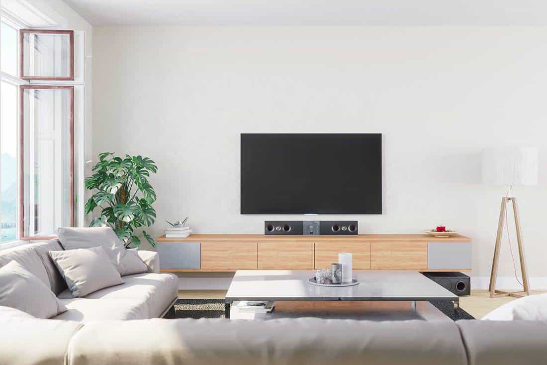 Interior of a modern, bright and airy living room with cozy sofa and TV