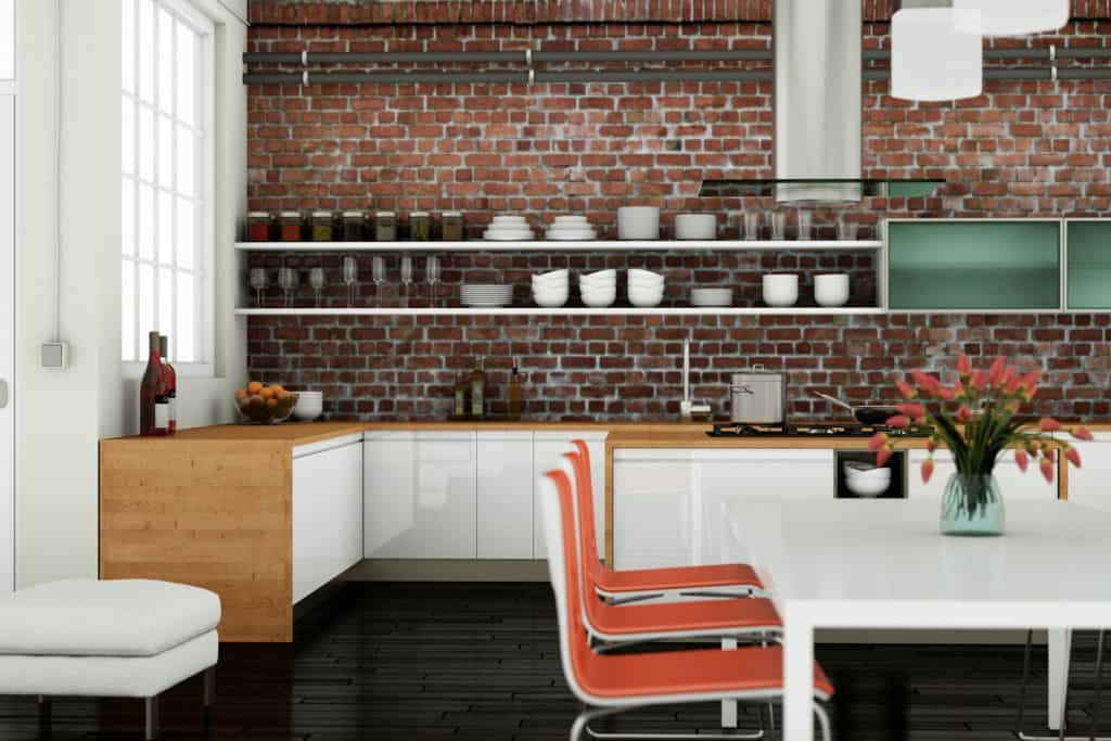 Interior of a modern kitchen with a brick designed backsplash, minimalist inspired cabinetry, and wooden kitchen countertop