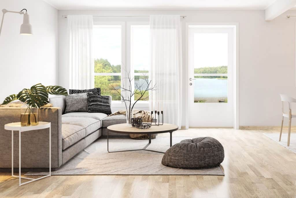 Interior of a modern living room with white walls, gray sectional sofa, round coffee table, and white curtains