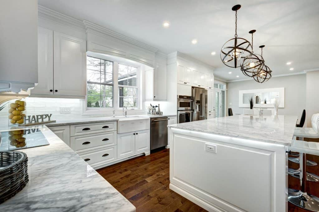 Interior of a modern white themed kitchen with white painted kitchen cabinetry and a white countertop breakfast bar