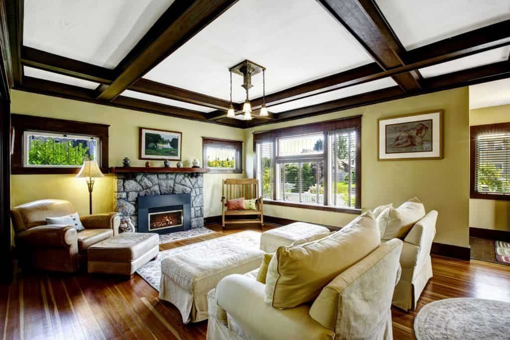 Interior of a rustic themed living room with light yellow painted living room walls, hardwood flooring, and white and dark brown combination coffered ceiling