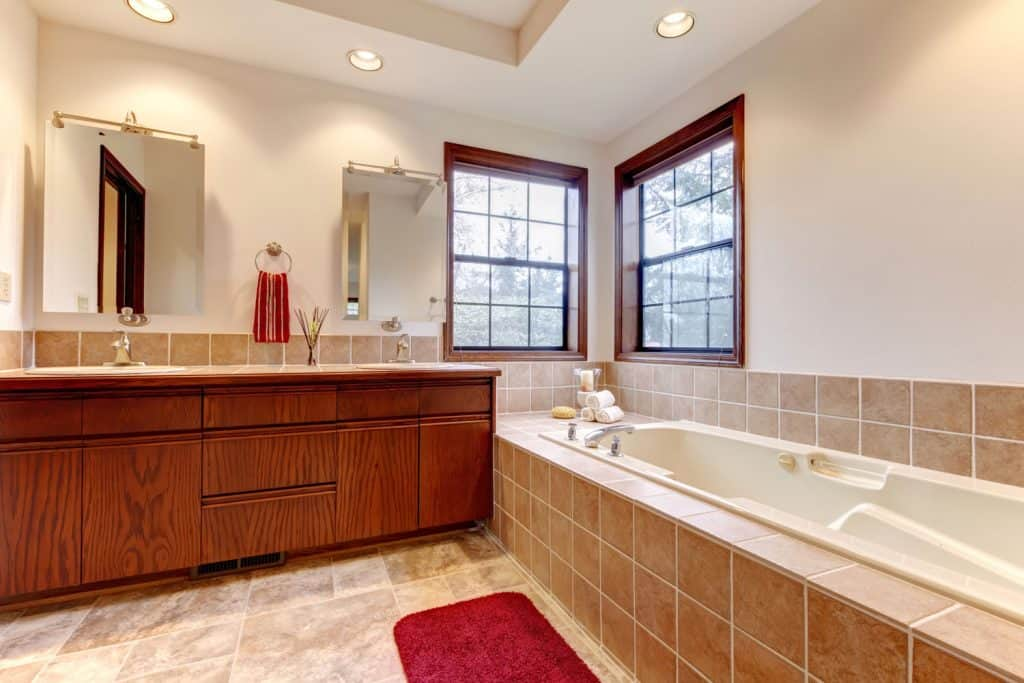Interior of an ultra modern bathroom with a bathtub, wooden hardwood cabinetry, and beige colored walls