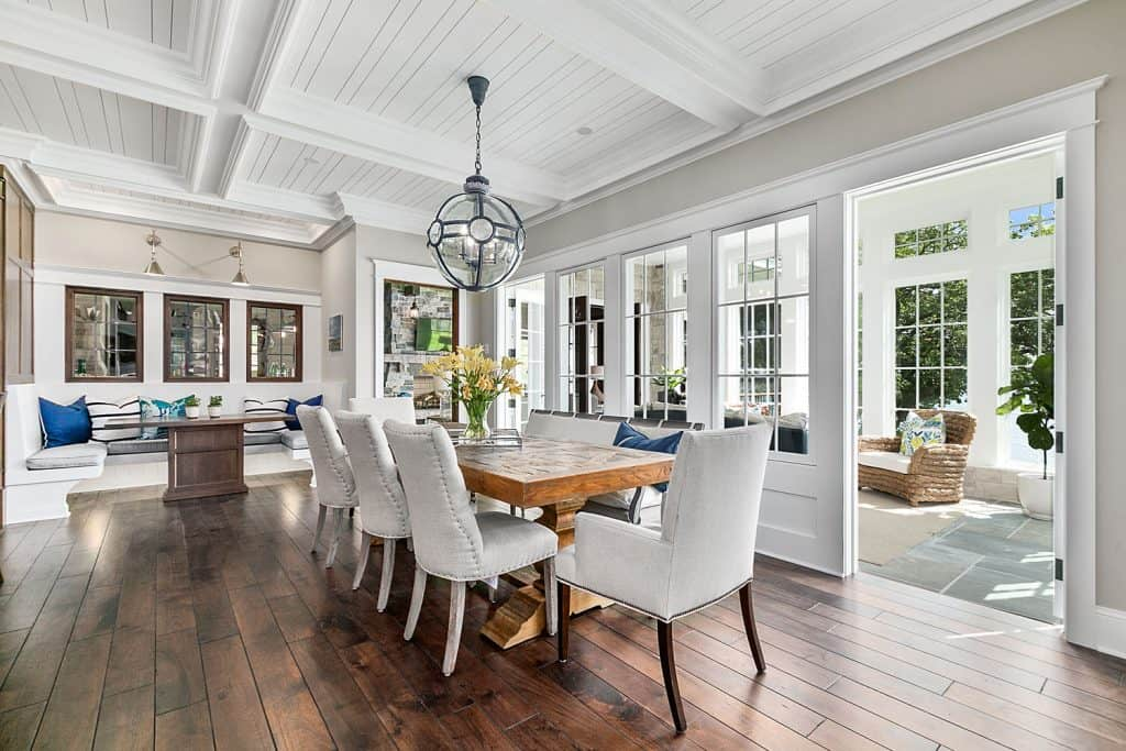 Interior of a vintage themed kitchen and dining area with wooden flooring, white dining chairs, and a white coffered ceiling