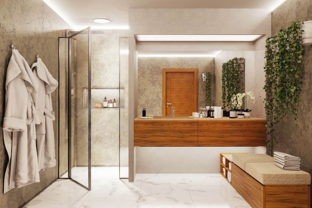 Interior of an earthy themed bathroom with hanging plants, wooden vanity, and a glass walled shower area