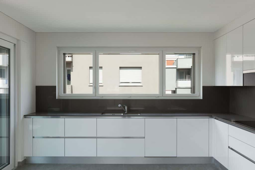 Interior of an ultra modern kitchen area with a dark tiled backsplash area