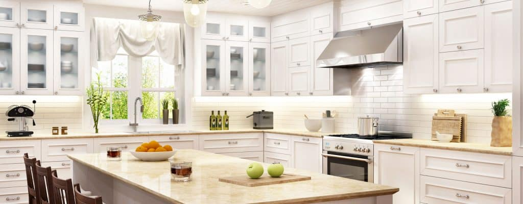 Interior of an ultra modern kitchen area with white paneled kitchen cabinetry and a granite countertop, breakfast bar