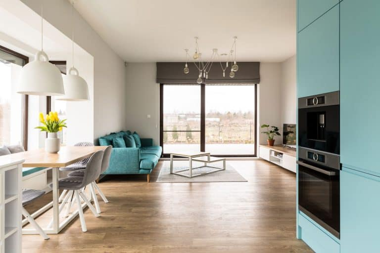 Interior of an ultra modern open space kitchen with laminated flooring, sky blue long sofa, and a sky blue kitchen cabinets, Can You Use Kitchen Paint In The Living Room?
