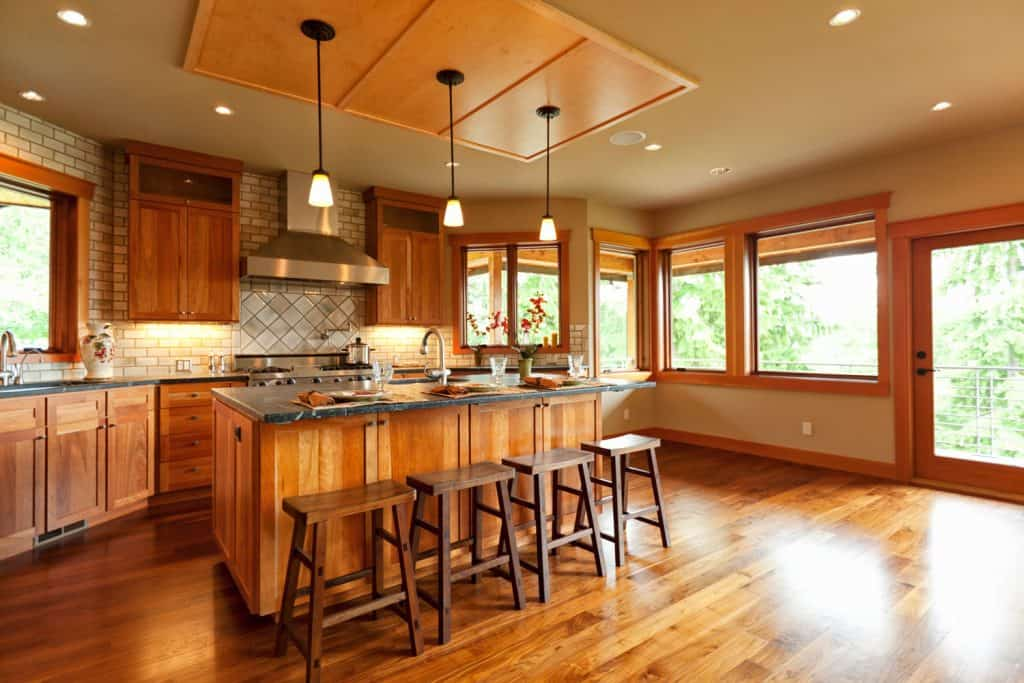 Interior of contemporary rustic interior of a modern kitchen area with wooden flooring, wooden window moldings, and a cozy breakfast bar