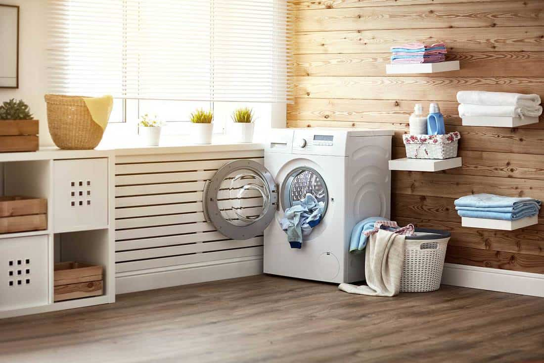 Interior of laundry room with washing machine at window, hardwood floor and walls