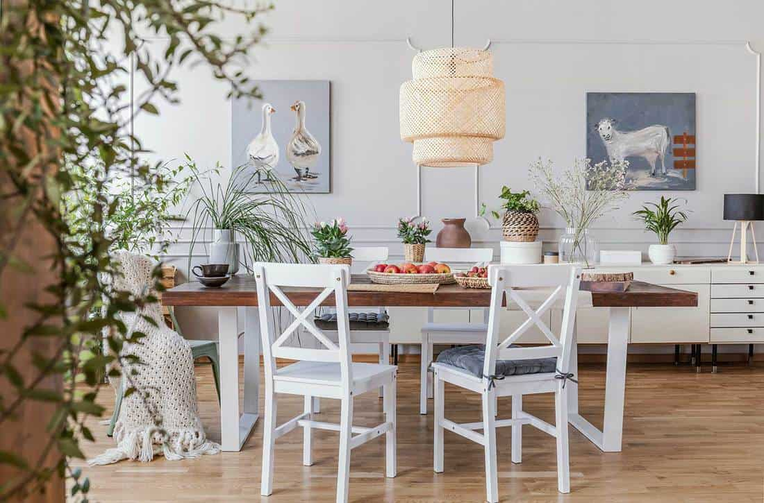 Lamp above wooden table in rustic dining room interior with white chairs and posters