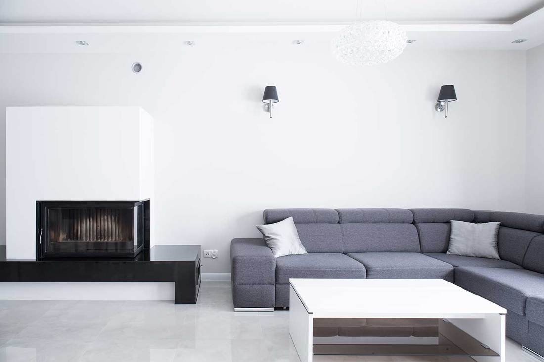 Large corner gray sofa in living room with white wall, fireplace and coffee table