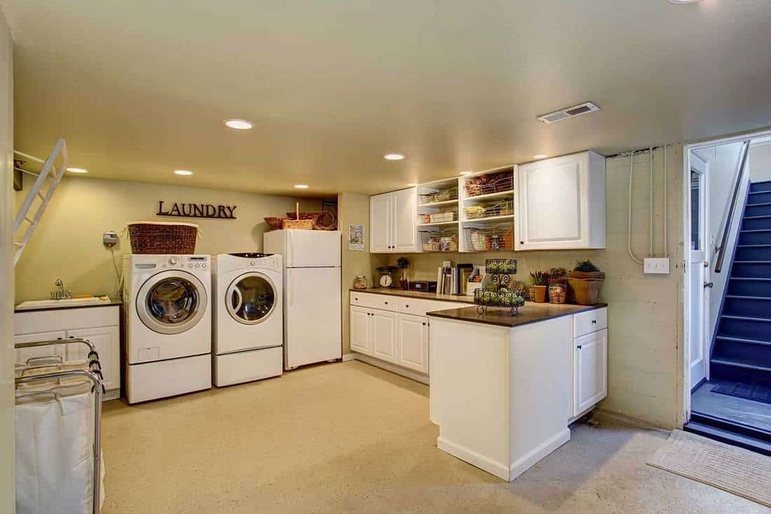 Large laundry room with appliances and cabinets