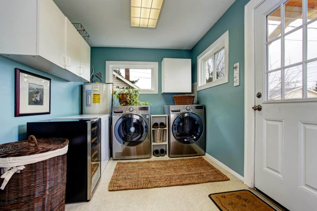 Laundry room with modern steel appliances and Tropical Turquoise wall paint