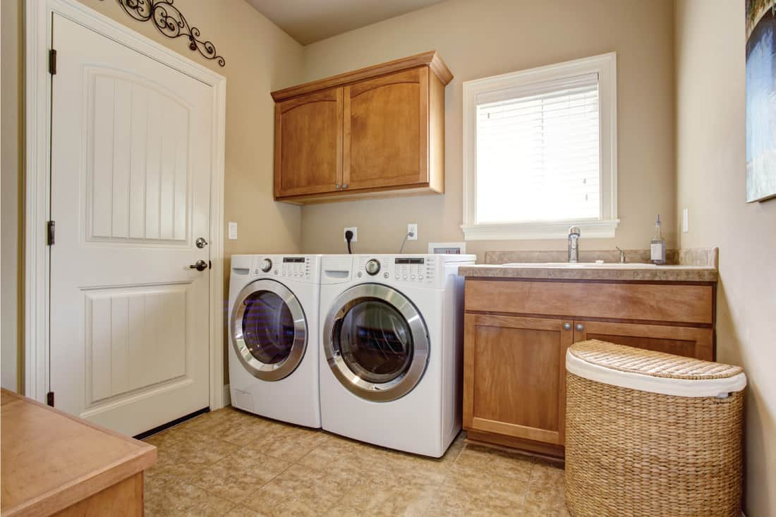 Laundry room with washer and dryer. classic warm Wood cabinets and tile floor