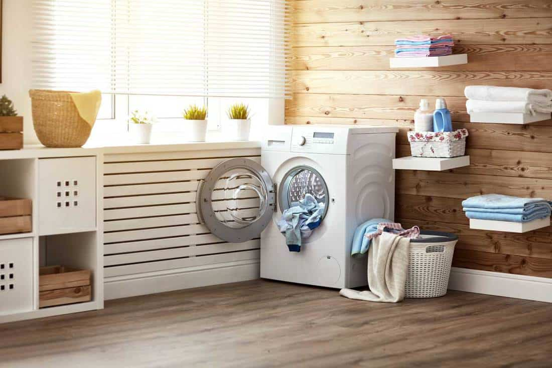 Laundry room with washing machine at window, hardwood floor and walls, 11 Farmhouse Laundry Room Ideas You Need To See