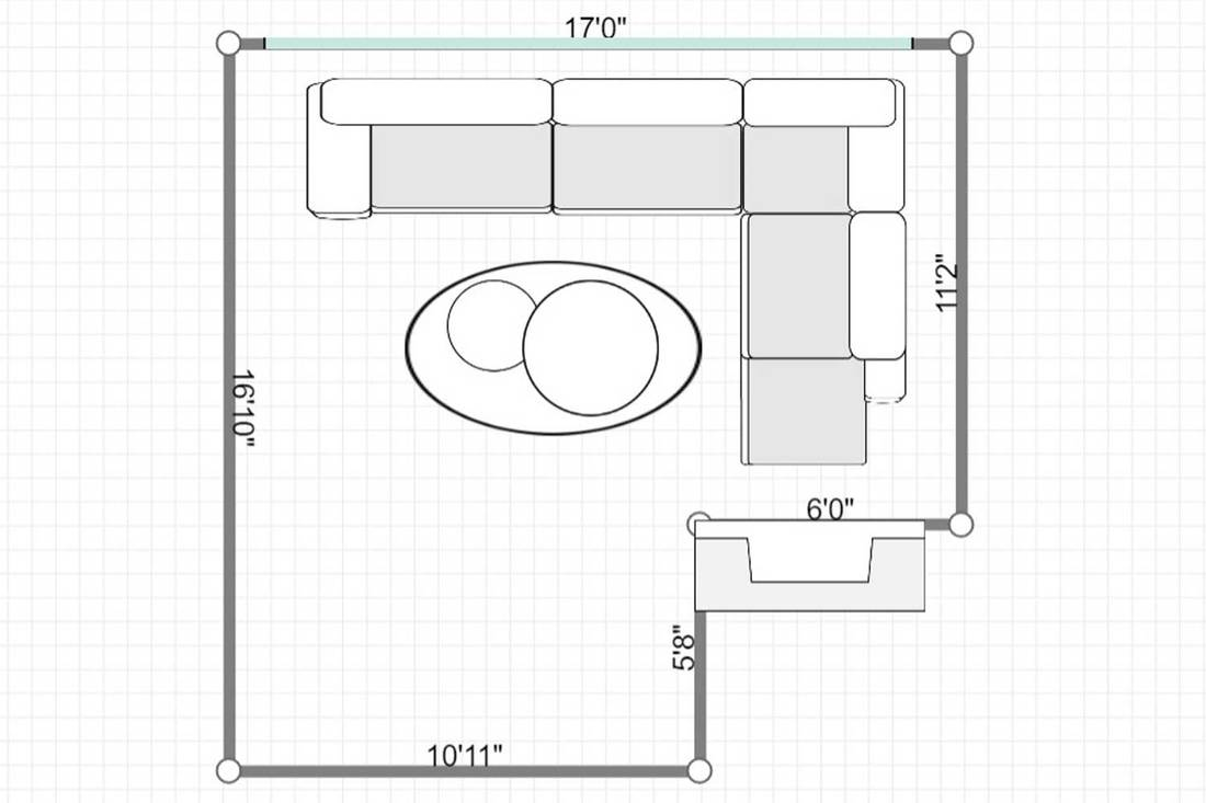 Layout of a wooden table on round rug near sofa in spacious living room interior with fireplace and painting