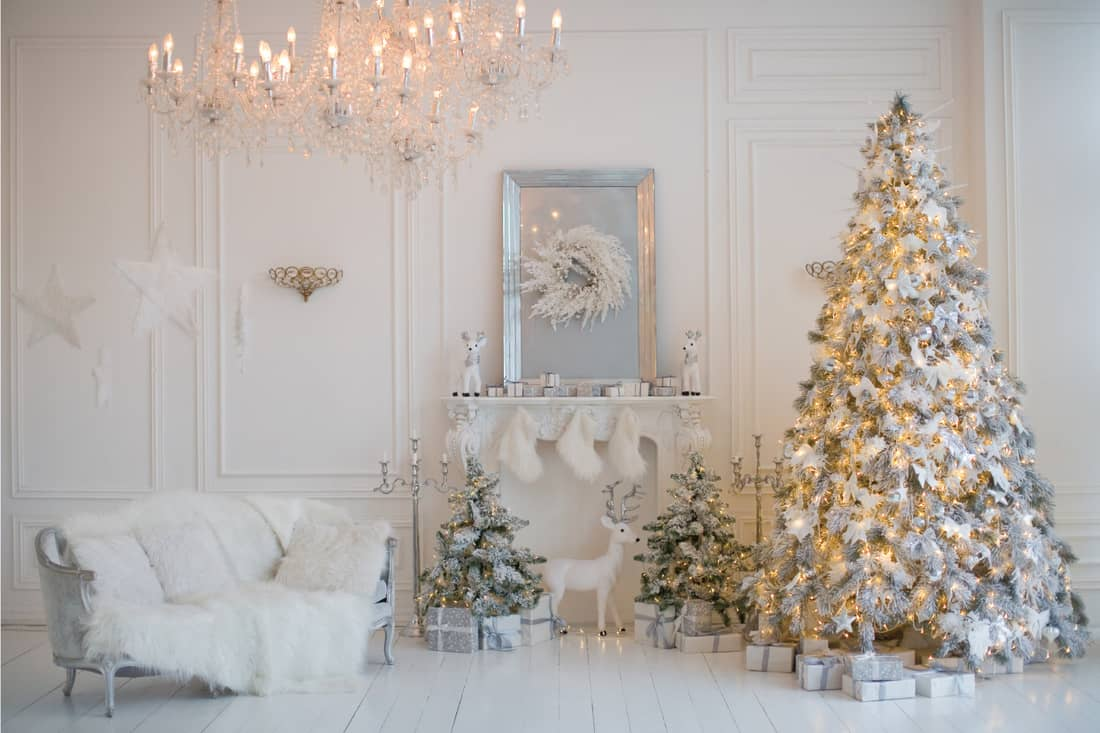 Living room with Christmas tree, white sofa, crystal chandelier, fireplace and white and silver decorations. all white holiday