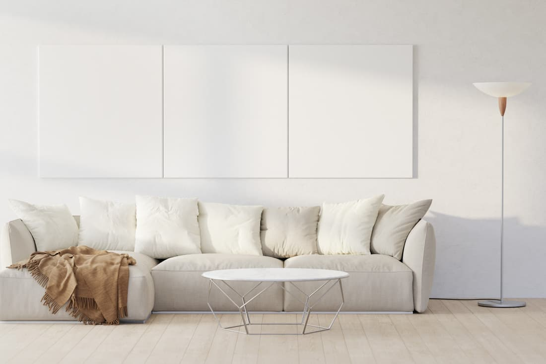 Living room with a white couch, table, floor lamp. white sectional